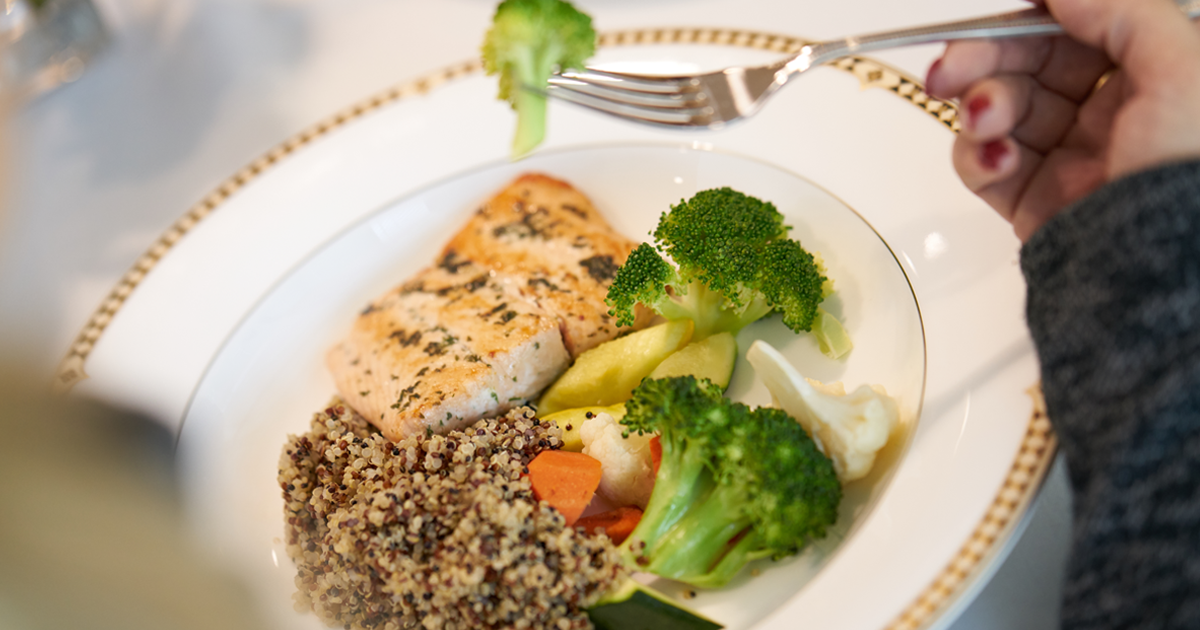 A plate of healthy food including salmon, broccoli, and wild rice
