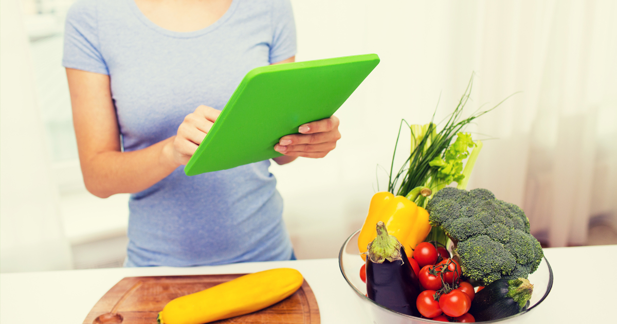 A female reviewing healthy recipes on a tablet in front of a kitchen counter topped with colorful vegetables