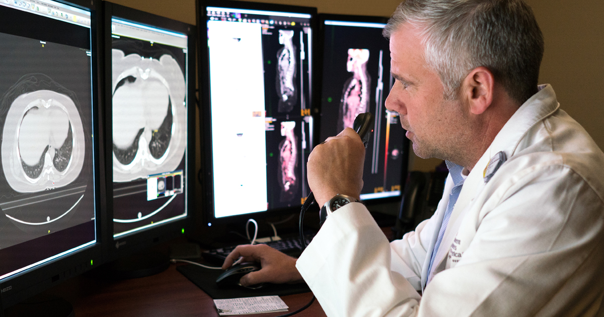 A male physician reviewing rare cancer screenings
